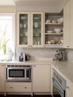 Open shelving in the corner is a good idea. Modern beige kitchen design. Microwave cubby built in.
