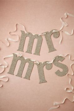 "Newly Minted Chair Signs at BHLDN -  Sparkly-bright silver glass glitter clings to carefree lowercase letters From Wendy Addison.     mr: 6""H, 12""W.     mrs.: 6""H, 15""W.     German glass glitter, cardboard, ribbon."
