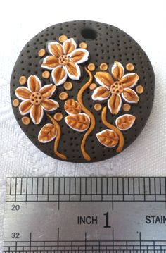 Polymer clay pendant, handmade with applique technique, one of a kind. Dark brown patterned with puncture marks, with bronze and white flowers and leaves and bronze dots. By Lis Shteindel.