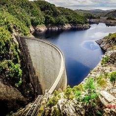 This is the Gordon Dam at Strathgordon in southwest Tasmania.  Home to Australia's longest vertical abseiling experience, adrenalin junkies get a kick out of descending down the 140 metre wall while it calmly holds back thirty times the water held in Sydney Harbour. The two and a half hour drive from the Hobart to Gordon Dam meanders through the stunning Derwent Valley and the magnificent southwest wilderness. #discovertasmania #strathgordon #gordondam #abseiling  Image Credit: Burhanu Dean