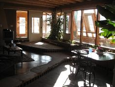 Inside main house of an Earthship, aka Rammed Earth Dwelling, separate from the hallway Greenhouse, image by Lindsay Tan *rock part of flooring Earth Bag, Rammed Earth, Natural Building, Earthship, Maine House, Sustainable Living, Life Is Good, House Design, Cob