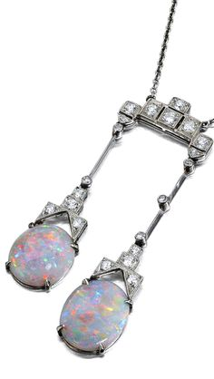 An Art Deco opal and diamond pendant/necklace Formed as a geometrically designed plaque set throughout with round brilliant-cut and single-cut diamonds, suspending two articulated knife-edge bar drops, each terminating in a geometrically designed mount set with round brilliant-cut and single-cut diamonds above an oval cabochon-cut opal, to a simple belcher-link neckchain, to original fitted case, length excluding drops 40cm