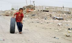 Iraq - A child plays on a street full of garbage in Basra, May 7, 2012. Photo by Abdulkareem Alamiry (RFE/RL)