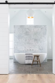 We love the combination of organic stone flooring, traditional barn doors and the contemporary Barcelona bath in this Nantucket Island bathroom by Elizabeth Norris Design, as seen on Remodelista. Photography by Brian Sager.