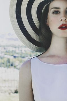 Lana del Rey outfit inspiration: White skater/midi dress with black and white big hat. Heavy flawless make up. love her.