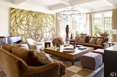 In the living room, an artwork by Aaron Young overlooks Patrick Naggar sofas from Ralph Pucci International that are covered in a Sahco fabric and accented with pillows in a velvet from Lee Jofa; the ceiling light is from Liza Sherman, and the vintage armchairs are clad in a Clarence House silk.