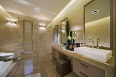 Modern bathroom design in beige color scheme. Double modern white basins, tub and glass-walled shower make up the key features