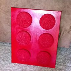 I came up with this the other night while trying to redecorate my boys room. They love LEGO and so do I:) It's simply one medium canvas, 6 round discs. I used foam discs from the Dollar store, they came two in a pack. I think I'll use wooden discs next time:) Then I positioned them into place and hot glued them onto the canvas. Last thing to do is paint! I used a red gloss spray paint to paint it:)