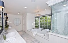 White bathroom with marble sink and glass shower