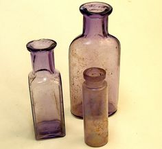 Group of small purple glass bottles.