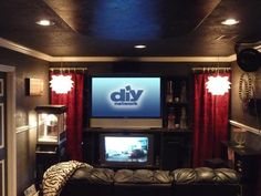 Family-Friendly Home Theaters: RMS user MacyGirl created a rich, Hollywood-inspired media room by integrating red, velvet curtains and modern light fixtures with the black walls. Classic film reels and a restored popcorn machine serve as decorative elements while pulling in those memorable details of a cinema experience. From DIYnetwork.com
