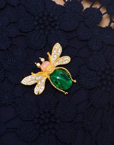 Add a touch of sparkle to your next ensemble with this fun embellished brooch. The bug shape is playful and on-trend with its gold rimmed edges, crystal wings and emerald body. Pin it on everything from jackets to dresses!