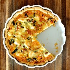 Pumpkin, Spinach and Feta Quiche 260g plain flour 145g butter, chopped 1 egg yolk 2-3 tablespoons iced water Filling 1 tablespoon olive oil 1 large onion, peeled and finely chopped 150g baby spinach (about 2 handfuls), rinsed 200g cream 5 eggs sea salt and cracked black pepper 500g roasted pumpkin pieces 100g feta cheese 2 tablespoon pine nuts 100g chedder cheese, grated