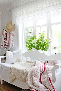 White painted entry bench in front of the windowsill with red quilts.  I also like the white lace curtain panel.