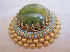 1960s, 1970s Goldtone Cadoro Bakelite Brooch, Marbled Green, Tuquoise Glass Stones. $ 75.00, via Etsy.
