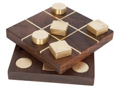 A perfect styling piece for your home as well as a functional game that's perfect for entertaining guests, this tic tac toe set features solid brass playing pieces and a hand-crafted walnut playing board with storage.