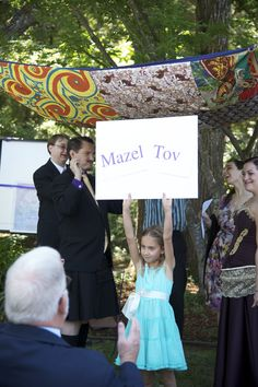 """""""Also, in order to cue our non-Jewish guests that it was time to yell """"Mazel Tov,"""" which is my favorite part of a Jewish wedding, we had my younger niece hold up a sign. Everyone was amused, and yelled obediently. """""""
