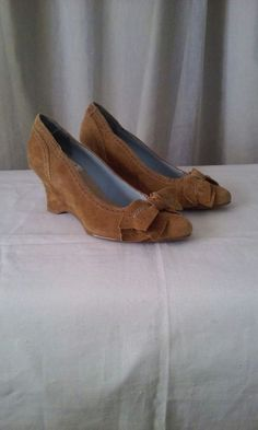 New (never used) - Brand new. Never worn. No shoe box.  Size 7  Color- Cognac  Material- 100% suede  Heel- 3 inches  Cute bowtie wedges with blue applique decorative stitching. See pictures.