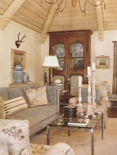 French country home - Living room by Charles Faudree.  Antlers, modern coffee table, candlesticks