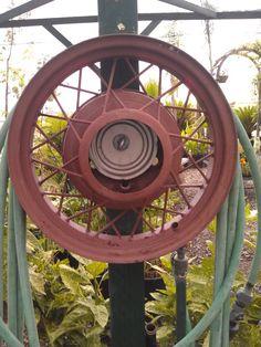 Repurposed antique Ford hub cap = garden hose reel. So cool!