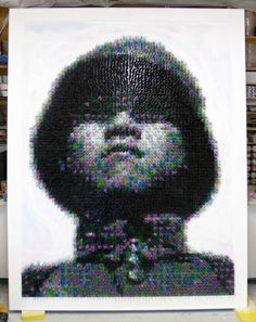 Made in China by Joe Black depicts the portrait of a Chinese soldier by photographer Robert Capa that appeared on the cover of LIFE magazine in 1938. Black glued over 5,500 multi-colored toy soldiers to a vertical surface to achieve the pointillistic effect.