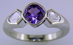 Purple sapphire set with two calf-head diamonds in a platinum ring.