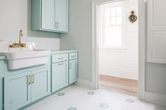 Tiffany blue laundry room is clad in white and Tiffany blue mosaic floor tiles accenting Tiffany blue cabinets donning brass pulls and a Tiffany blue countertop holding an apron sink finished with a brass vintage faucet between Tiffany blue upper cabinets mounted to a light gray wall.