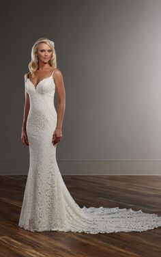 This designer sheath wedding gown from Martina Liana features graphic lace over ivory Imperial crepe. Its sweetheart neckline is accented perfectly with sexy spaghetti straps. The back zips up under pearl buttons and flows perfectly into a sleek chapel train.
