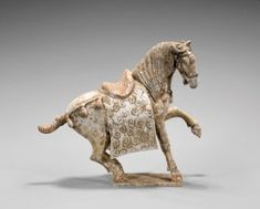 """TANG DYNASTY POTTERY HORSE Chinese Tang Dynasty painted pottery model of a horse; standing with one front foot up, mounted with saddle and elaborate blanket decorated with swirl accents, and adorned with moulded bells; with much original slip remaining; L: 12"""" (approx.); on fitted wood stand, and in glass display case"""