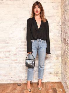 A camisa é uma daquelas peças de roupa que funcionam diferentes ocasiões do dia. Em look básico, mas descolado, Jeanne Damas usa uma camisa preta com calça jeans reta cintura alta. A graça fica por conta dos acessórios prateados.