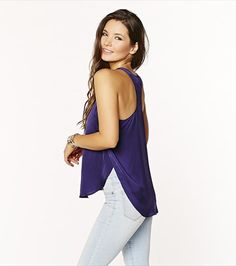 With a satin finish and dropped armholes, this purple racerback tank is perfect for going from desk to drinks!