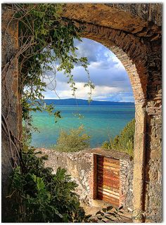 Looking through an antique archway onto an emerald and sapphire Italian lake. Lake Bolsena, region of Lazio, Italy, North of Rome.