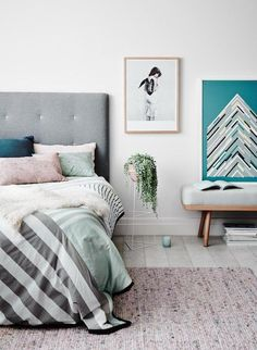 Bedroom home decor | modern look, bedding with throw pillows, stripes, and grey headboard. house plant and framed prints as a gallery wall for decoration