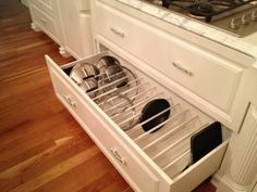 A set of tension rods to store cookware vertically. | 23 Things Anyone With A Tiny Kitchen Needs