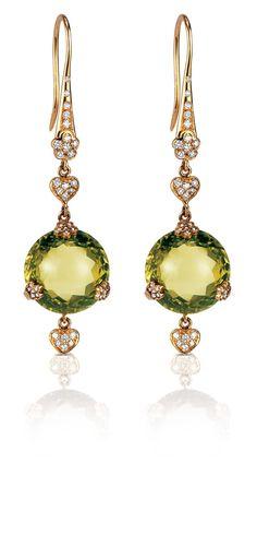 Ces boucles d'oreille sont le vert et l'or. Ils sont élégants. Ils ont l'air cher.