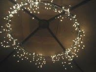 1 hula hoop (spray painted) + 2 strings of icicle lights and a bit o' duct tape = magnificent  chandelier. (Want to do this on my parents' back patio!)