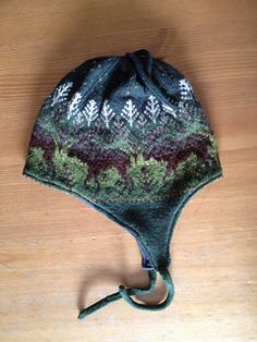 FREE PATTERN...Moose walk through the trees on this earflap hat. Designed for cold weather, it is knit with two and occasionally three colors per row and has a sewn-in lining. Worked at 7 1/2 stitches to the inch, it is sized for an adult man, and size changes are best made by changing the needle size and gauge. The pattern uses approximately 30 yards each of 16 colors of greens and browns and is perfect for the knitter with the large stash.