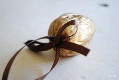 un ornement sapin de Noël - noix doré et décoré d'un ruban fin et marron