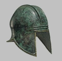 A GREEK BRONZE ILLYRIAN HELMET   ARCHAIC PERIOD, CIRCA 6TH CENTURY B.C.   Hammered from a single sheet, of domed form, with a wide flaring neck-guard, two sets of three raised parallel ridges running front to back across the crown, the raised ridge around the perimeter with evenly-spaced gilt rivets along the edge, each cheek-guard perforated at the forward tip, with two horizontal ridges across the brow  11 in. (28 cm.) high