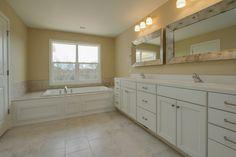Large custom soaking tub. White shaker cabinets. Ceramic floors.