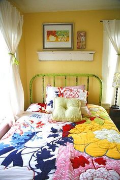 Cheerful, cozy room. I would lower the brightness and contrast in the colors in the quilt, but I love the contrast of the design of the quilt contrasted with the quiet simplicity of the bedstead and wall.
