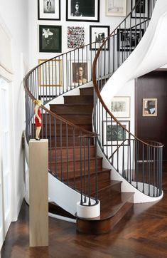 Frog Hill Designs Blog Love the image artwork collage displayed up the curved stairway in this entryway.  It leads the eye up the stairs and provides interest along the way. #curvedstaircase #artcollage #entryway  See more at www.froghilldesigns.net/blog