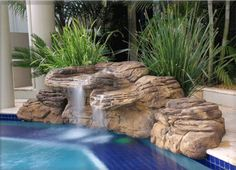 Swimming Pool:Modern Pool Waterfall With Decorative Plants Also White Poles  Design Natural Looking Swimming Pool Designs With Waterfalls And Round Rock