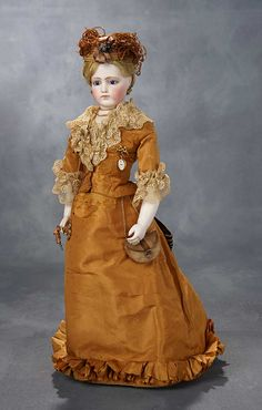 French bisque poupee, circa 1875. Wearing beautiful bronze silk gown, matching bonnet, lorgnette, watch with fob, leather purse, undergarments, stockings, tan leather shoes.