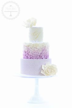 A beautiful wedding cake in ombre lavender tones and featuring sugar flowers.