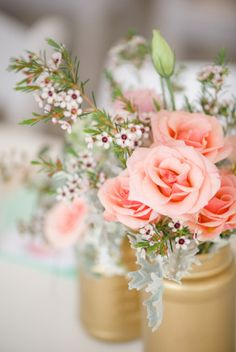 Peach roses and white wax flower used for simple wedding centerpiece in gold jars.