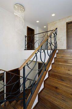 Designové závěsné svítidlo značky Kare a dřevěné schodiště s kovovým zábradlím na míru. Na tmavší stěně u dveří v patře je speciální stěrka, které majitelé říkají kávové skvrny.