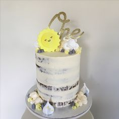 You are my sunshine first birthday cake - semi naked with cloud meringues, a glittery gold cake topper and a sugarpaste sunshine!