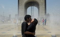 A young couple kisses in the fountain during the celebration of International Women's Day, at Revolution Square in Mexico City, on March 8, 2012. (Yuri Cortez/AFP/Getty Images)