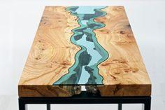 A mesa Elm River Console Table feita de madeira pelo designer Greg Klassen. Inspirada na natureza, rios e lagos em vidro cortam a superfície.